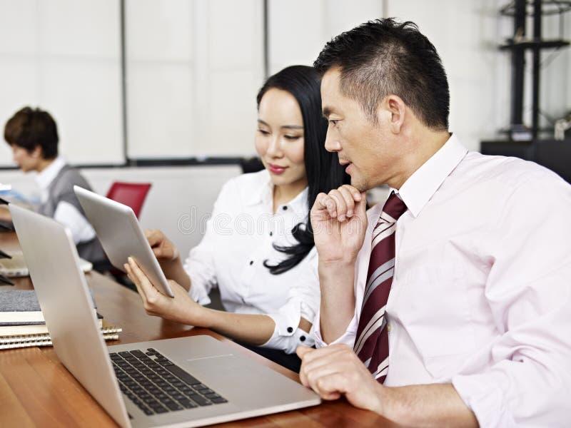 亚裔工作在办公室的商人和妇女 免版税库存图片