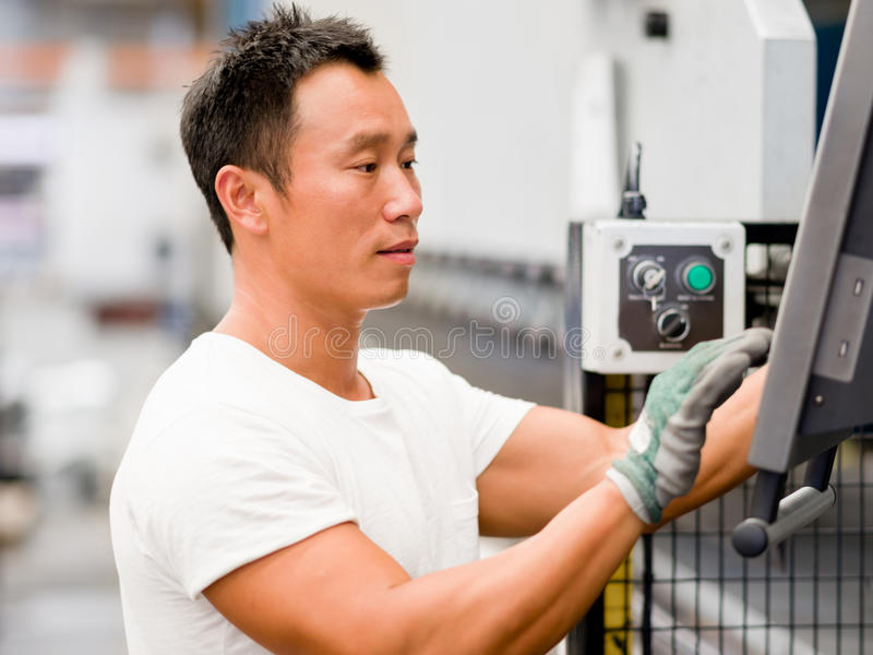 亚裔工作者在工厂的生产设备 库存图片