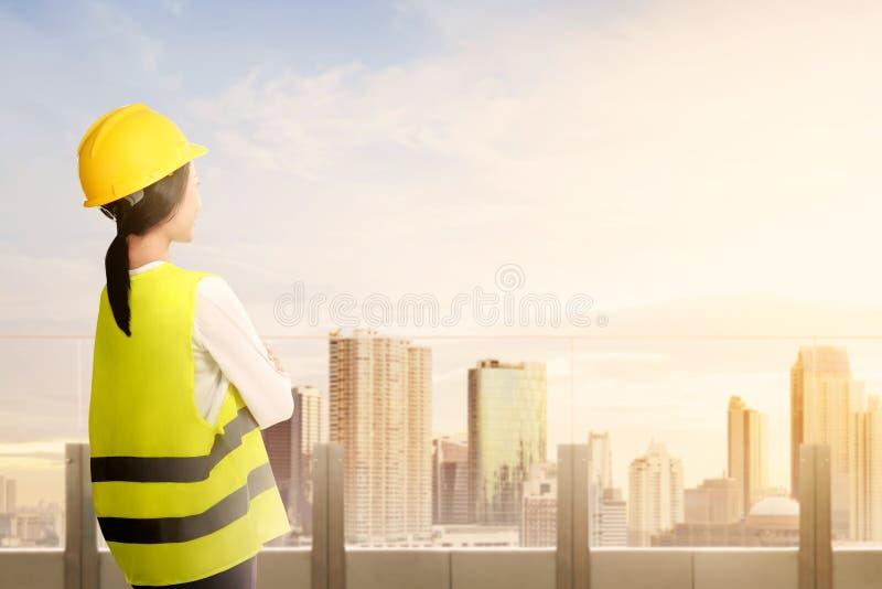 亚裔工作者妇女背面图安全背心、手套、黄色盔甲和防毒面具身分的在现代大阳台和看 免版税库存图片