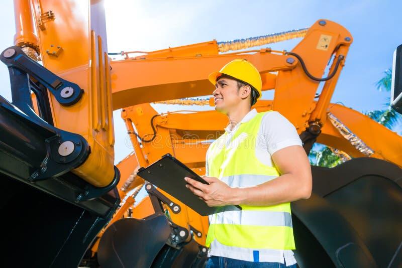 亚裔工程师控制铁锹挖掘机 免版税库存图片