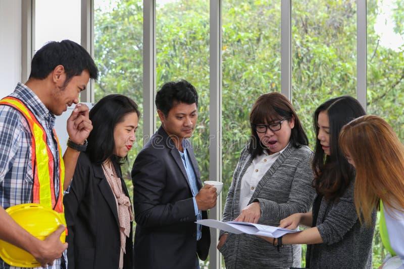 亚裔工程师画象 年轻建筑队在工作 办公室工作者观察文件在候选会议地点 工程师和 库存照片