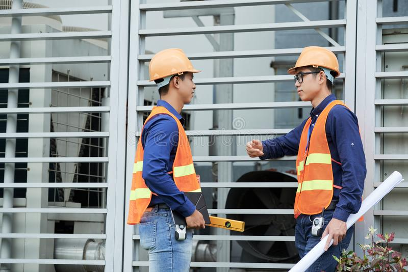 亚裔工程师谈话在墙壁附近 免版税库存图片