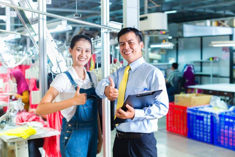 亚裔工头在给训练的纺织品工厂 免版税库存照片