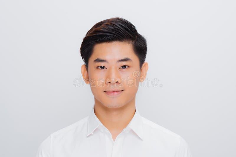 亚裔帅哥,微笑和笑隔绝在白色背景,软的焦点 免版税库存照片