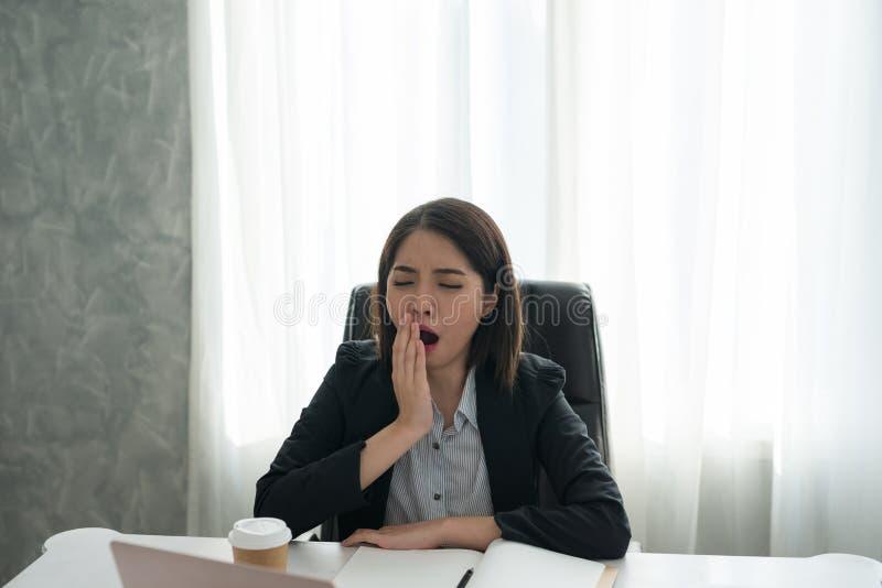 亚裔年轻企业女孩困打呵欠与工作在办公室 库存图片