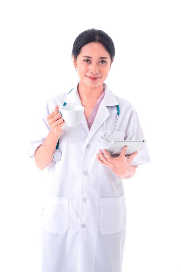 亚裔年轻女人医生画象制服和听诊器的在脖子 手藏品与片剂的杯子咖啡和看照相机 免版税库存图片