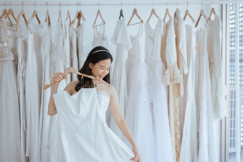 亚裔年轻女人新娘尝试在婚纱在现代婚礼,愉快和微笑 免版税库存照片