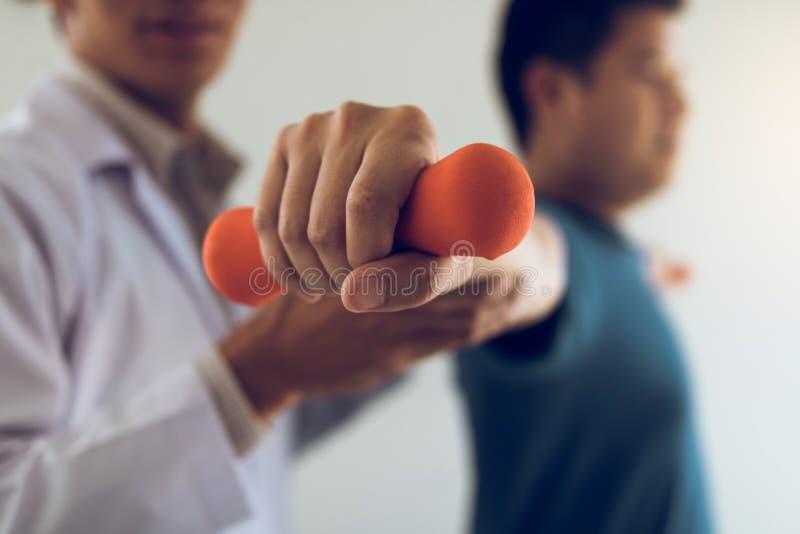 亚裔年轻男性有举的哑铃锻炼的生理治疗师帮助的病人在办公室 免版税库存图片