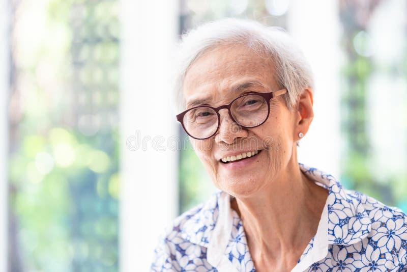 亚裔年长妇女的关闭显示健康平直的牙,画象资深妇女微笑的感觉的玻璃的愉快,美丽 免版税图库摄影