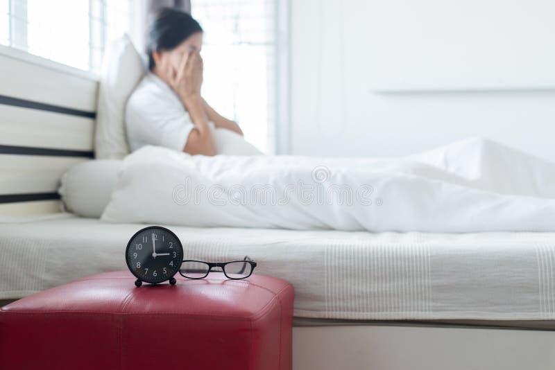 亚裔年长妇女Blured坐有消沉的卧室孤独有头疼,精神障碍医疗保健概念 免版税库存图片