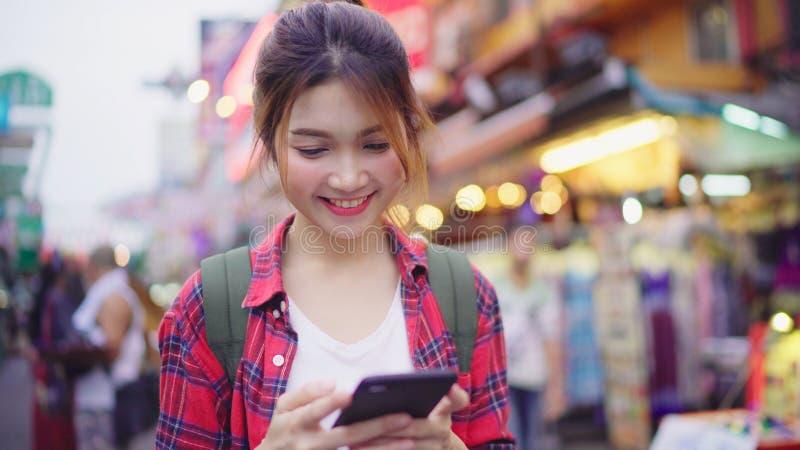 亚裔微笑和使用智能手机旅行的单独假日的妇女旅游背包徒步旅行者户外在城市街道上 库存图片