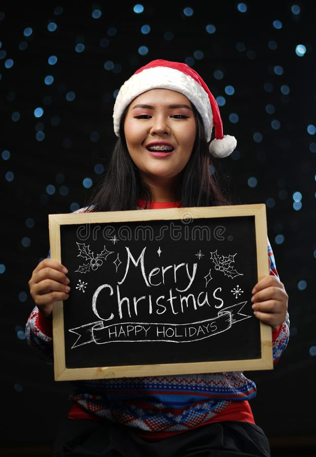 亚裔快活女孩佩带的圣诞节毛线衣和圣诞老人帽子的藏品 库存照片