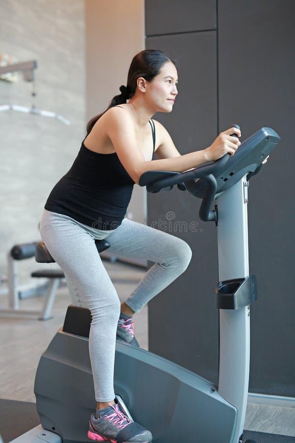 亚裔怀孕的女性画象做锻炼在体育屋子里,骑自行车,健康母性概念 图库摄影