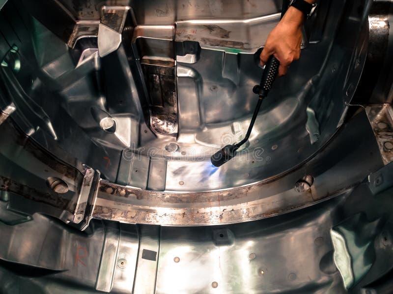 亚裔技术员人手工燃烧在钢模表面  库存图片