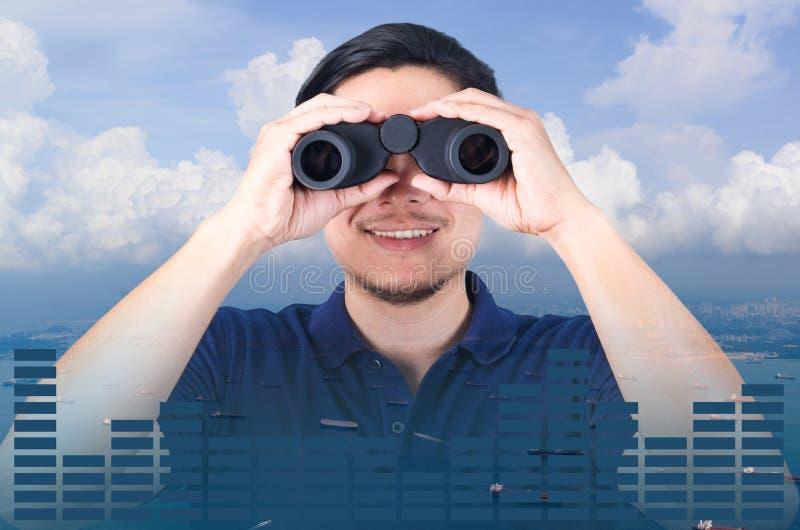 亚裔投资者两次曝光有双筒望远镜的 在从空中和财政图表的海景视图 免版税库存图片