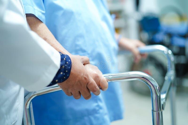 亚裔护士生理治疗师医生关心,帮助和支持资深或年长与步行者的老妇人妇女耐心步行 免版税库存照片