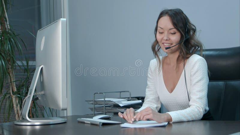 年轻亚裔操作员谈话与顾客在国际电话中心 免版税库存照片