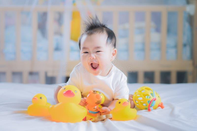 亚裔新出生的婴孩坐并且播放动物玩具 图库摄影