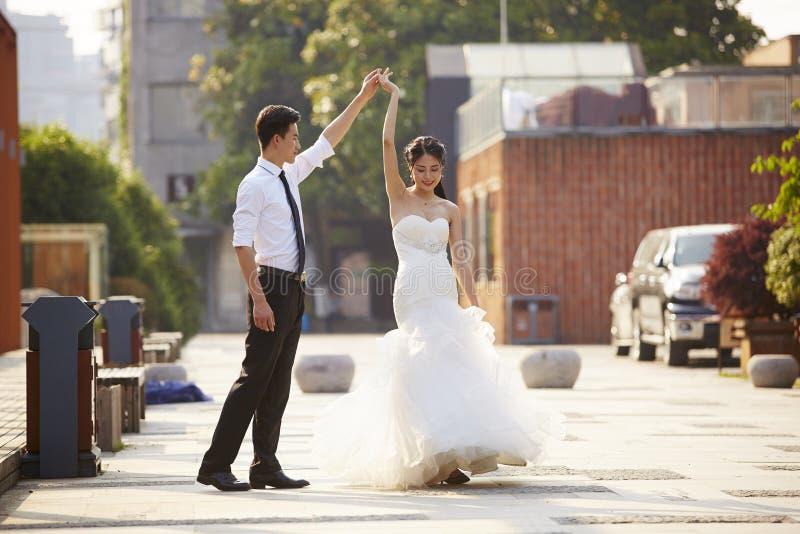 亚裔新娘和新郎跳舞在停车场 库存照片