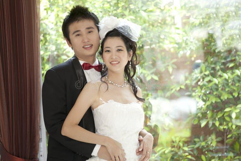 亚裔新郎和新娘夫妇婚礼衣服的 库存图片