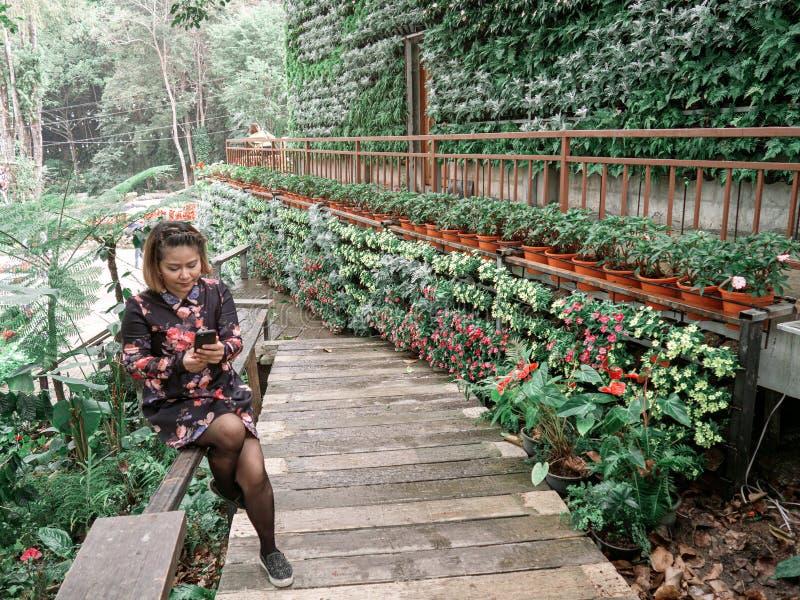 亚裔旅客坐 妇女穿花和黑色礼服 女性拿着手机并且看它 图库摄影