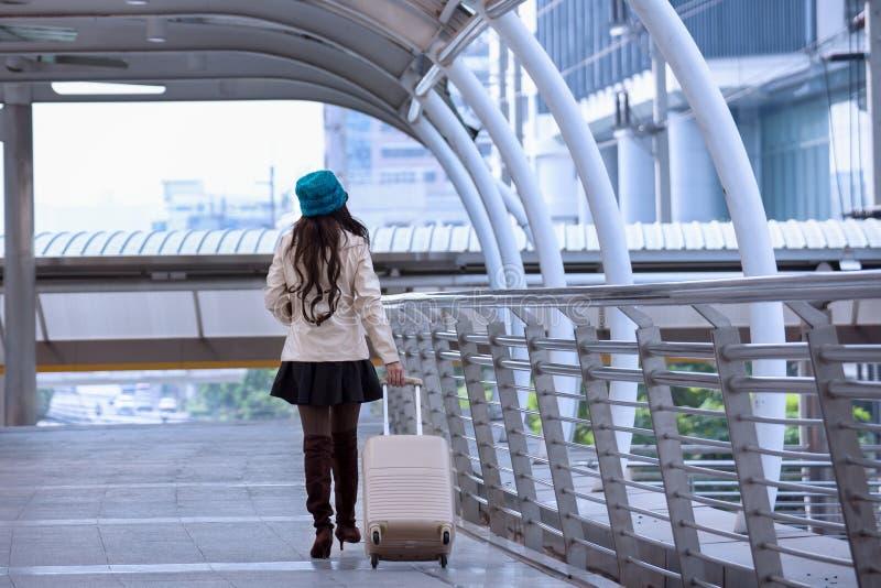 亚裔旅行妇女佩带的毛线衣外套、蓝色毛线帽子和举行 免版税图库摄影