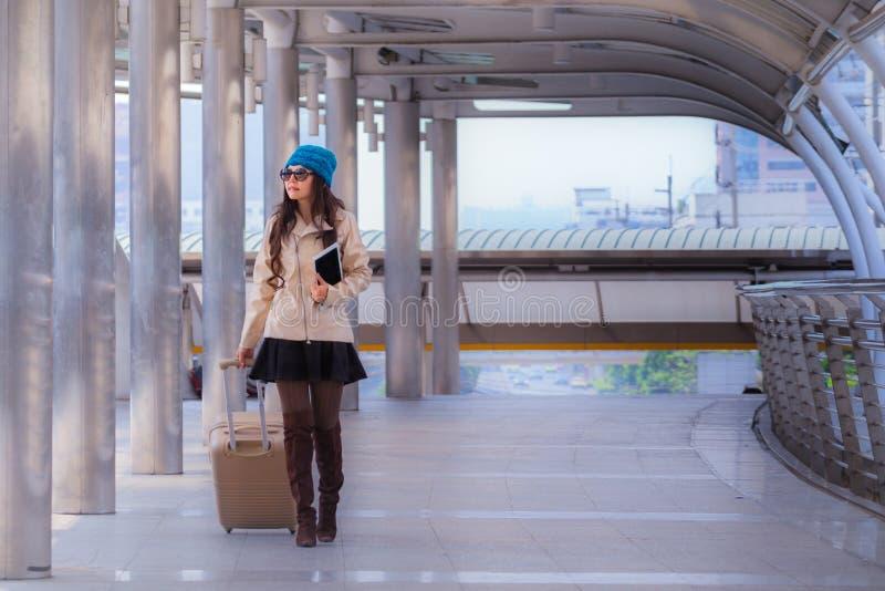 亚裔旅行妇女佩带的毛线衣外套、蓝色毛线帽子和举行 免版税库存图片