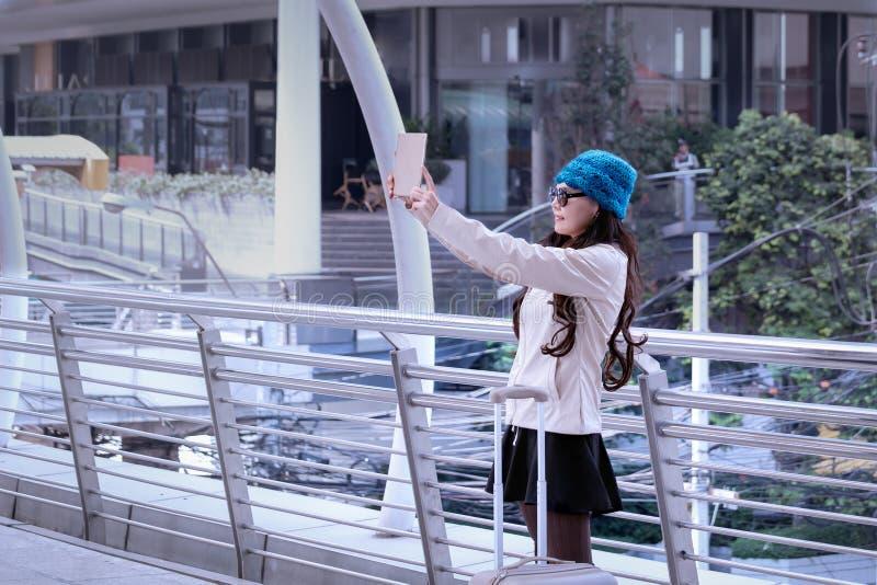 亚裔旅行妇女佩带的毛线衣外套,有lugg的蓝色毛线帽子 库存照片