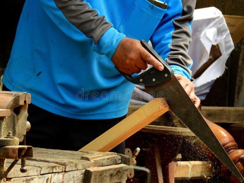 亚裔木匠切开木材沿着线 免版税图库摄影