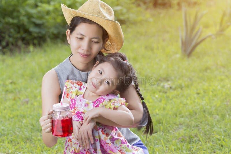 亚裔母亲和女儿在庭院里 免版税库存图片