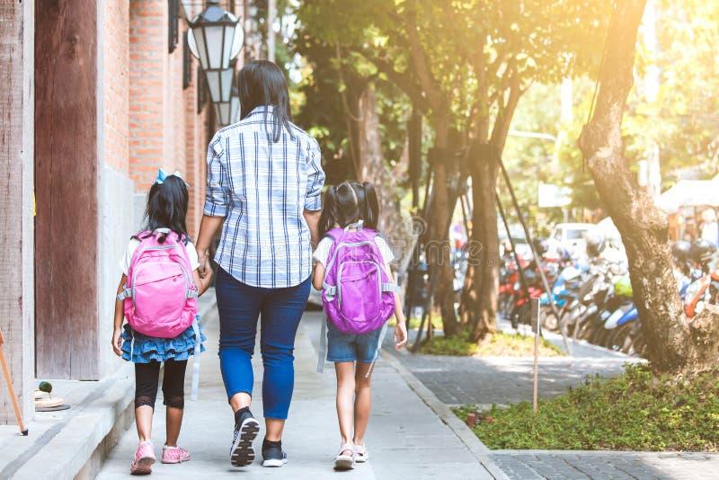 亚裔母亲和女儿学生女孩用背包藏品手和去一起教育 库存图片