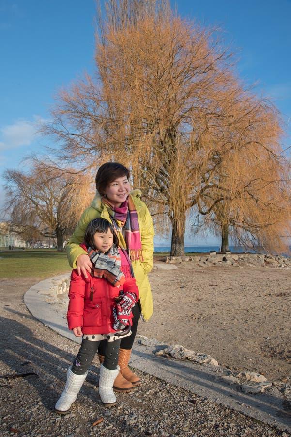 亚裔母亲和女儿,纳沙泰尔镇在冬天,瑞士,欧洲 图库摄影