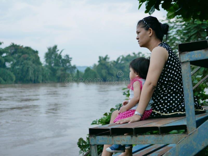 亚裔母亲和她的小女儿由她的看黑暗的泥泞的河的边在降雨量以后 免版税库存照片