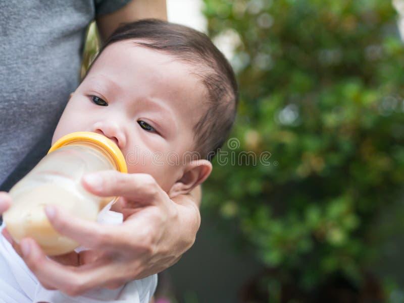 亚裔母亲哺乳瓶她的婴孩在庭院里 库存照片