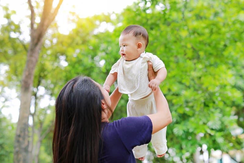 亚裔母亲在有早晨阳光的夏天庭院投掷她的胳膊的婴儿男婴 免版税图库摄影