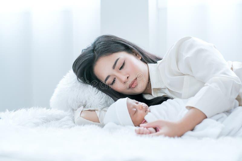 亚裔母亲躺在床上,小心地看着她刚出生的婴儿,她睡在白色床上,白天亮 免版税库存图片
