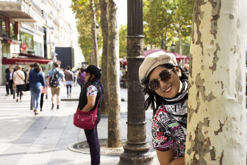 亚裔泰国妇女嬉戏和旅行参观在L'avenue des爱丽舍的边路 免版税库存图片