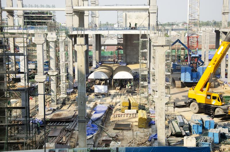 亚裔泰国工作者和大量手段运作的建造者新的大厦在工地工作高层建筑物在曼谷,泰国 免版税库存图片
