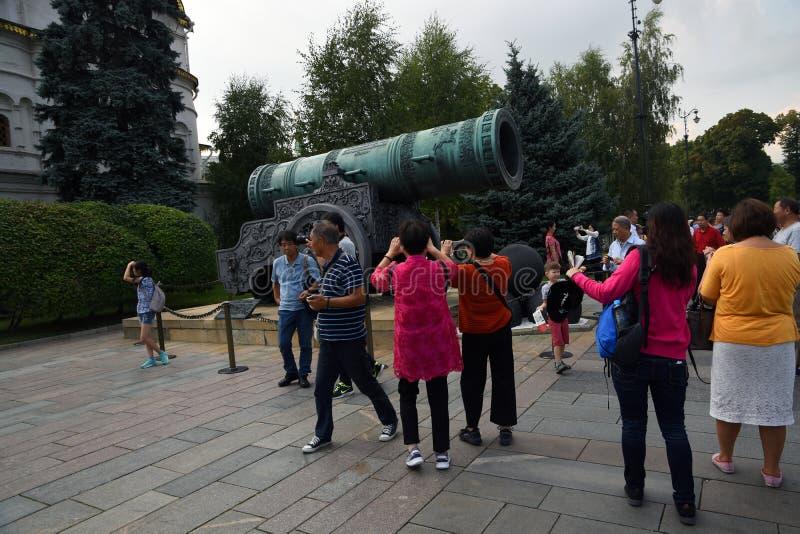 亚裔游人在克里姆林宫为Cannon国王照相 免版税库存照片