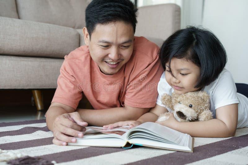亚裔父亲和女儿在地板读了书在房子,自我学习概念里 库存照片