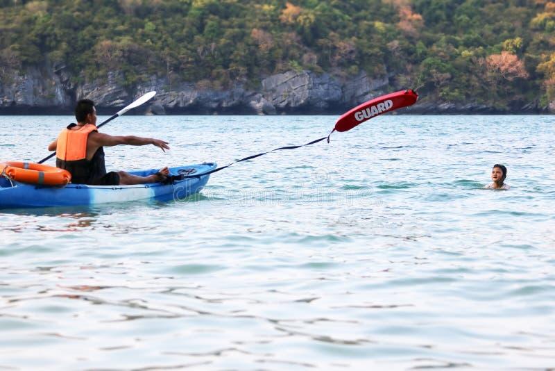 亚裔父亲和女儿是教和训练救生员或抢救在海滩 免版税图库摄影