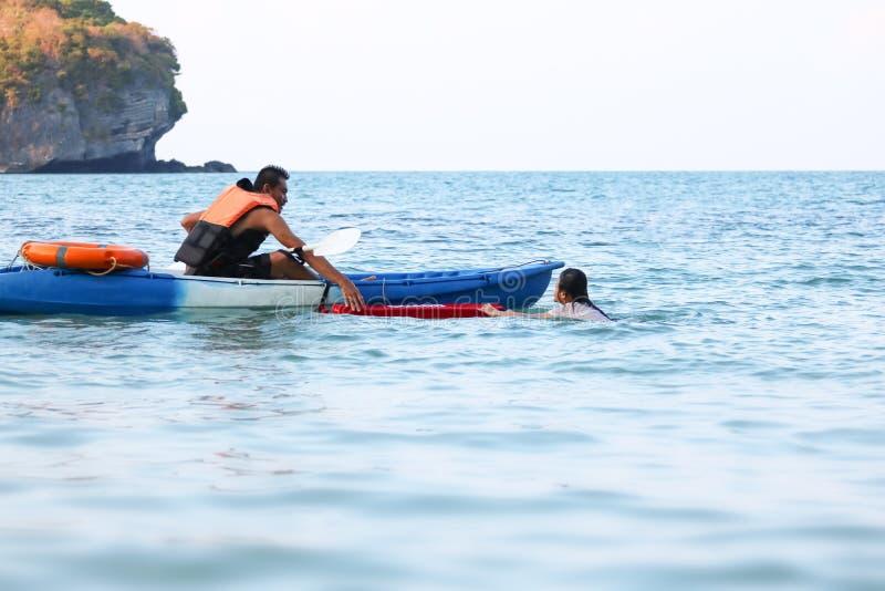 亚裔父亲和女儿是教和训练救生员或抢救在海滩 库存图片