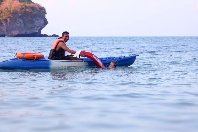 亚裔父亲和女儿是教和训练救生员或抢救在海滩 免版税库存照片