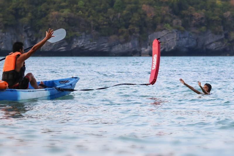 亚裔父亲和女儿是教和训练救生员或抢救在海滩 免版税库存图片