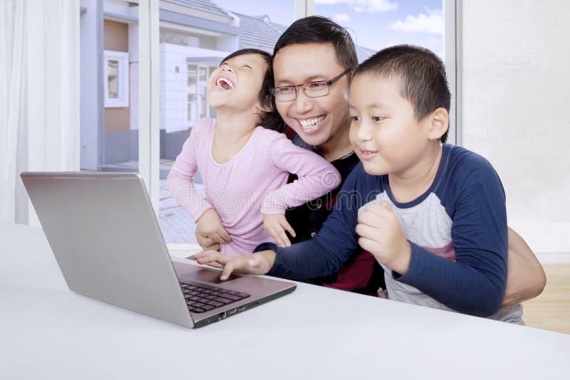 亚裔父亲和他的使用膝上型计算机的孩子 库存图片
