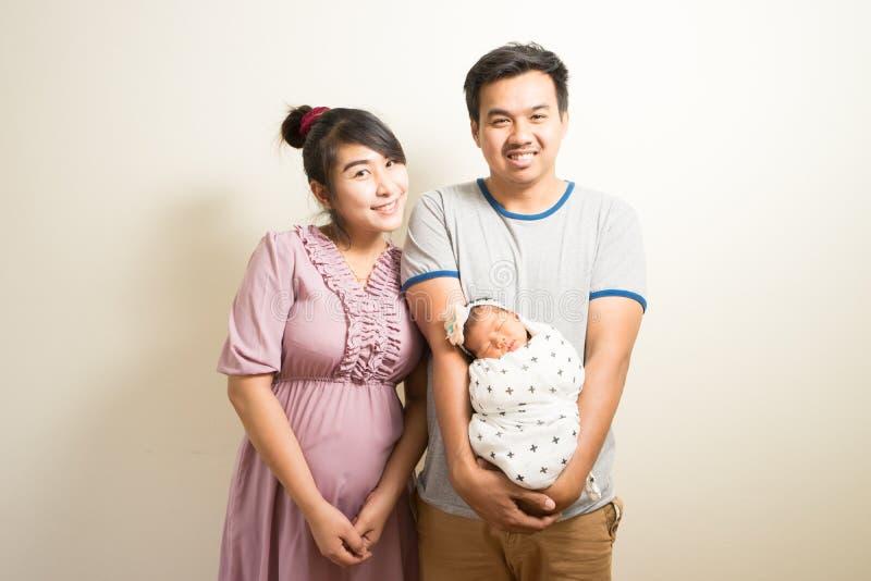 亚裔父母和六个月画象女婴在家 库存照片