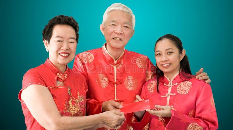 亚裔父母给红色包围给女儿农历新年 免版税库存图片