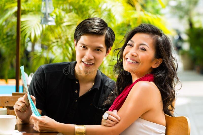 亚裔男人和妇女在餐馆 免版税库存图片