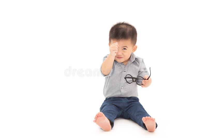 亚裔男婴坐和显示与手指和佩带的企业衬衣和举行玻璃的微型心脏 免版税图库摄影