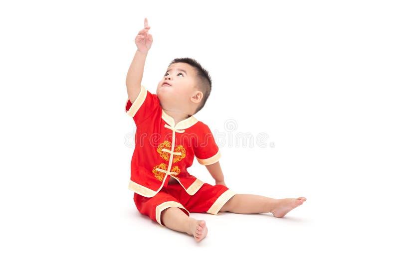 亚裔男婴坐,并且指向顶面和佩带的传统中国衣服,为中国新装饰 免版税库存照片